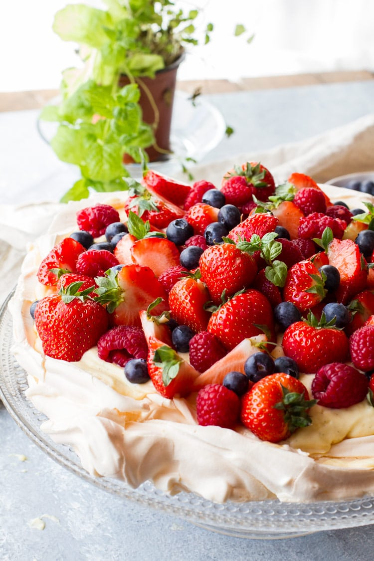 Closeup of the pavlova recipe with a lot of fresh berries and mint.