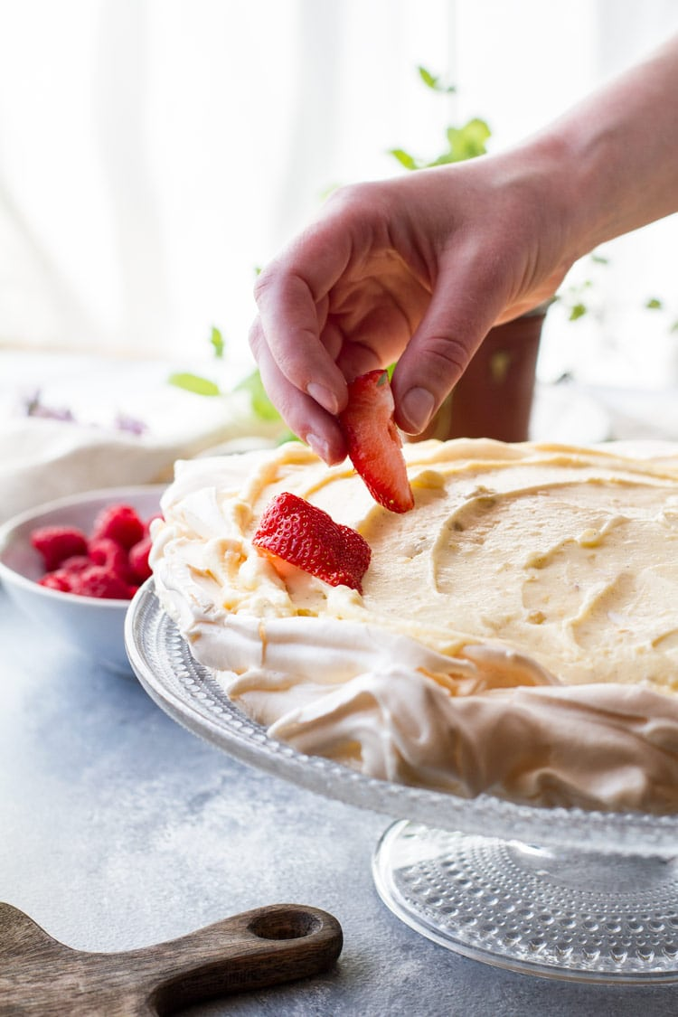 Placing sliced strawberries on pavlova cake with vanilla pastry cream