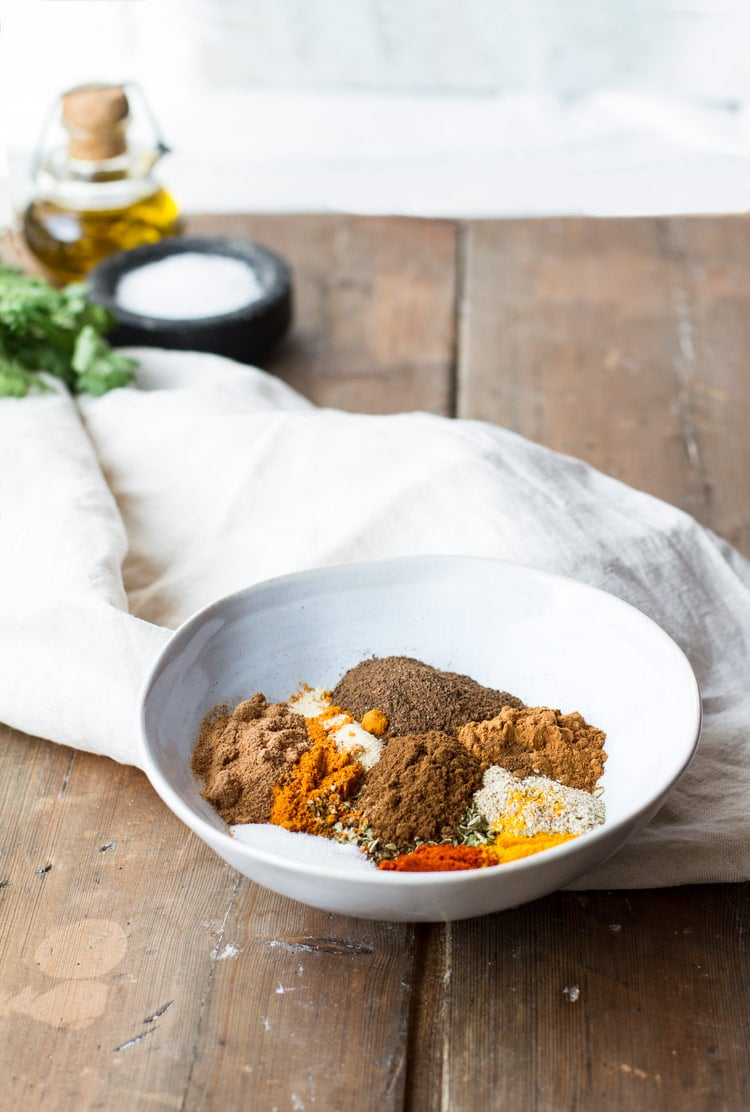 Shawarma spices separated in a small bowl. Wooden background with beige kitchen towel and white wall.