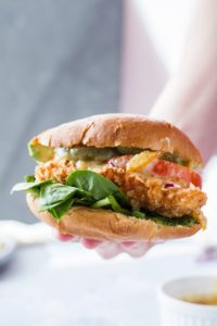 A panko chicken burger with lettuce, tomatoes and pickles.