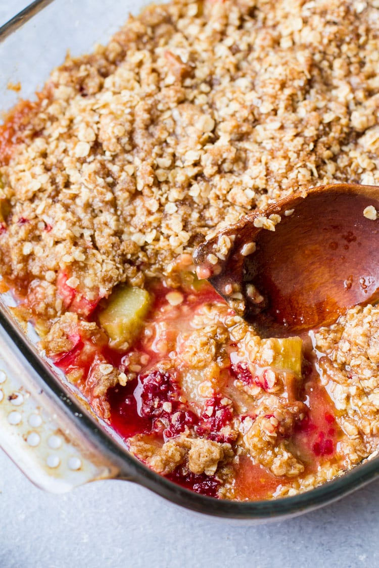 Closeup of the rhubarb crisp and a wooden spoon.