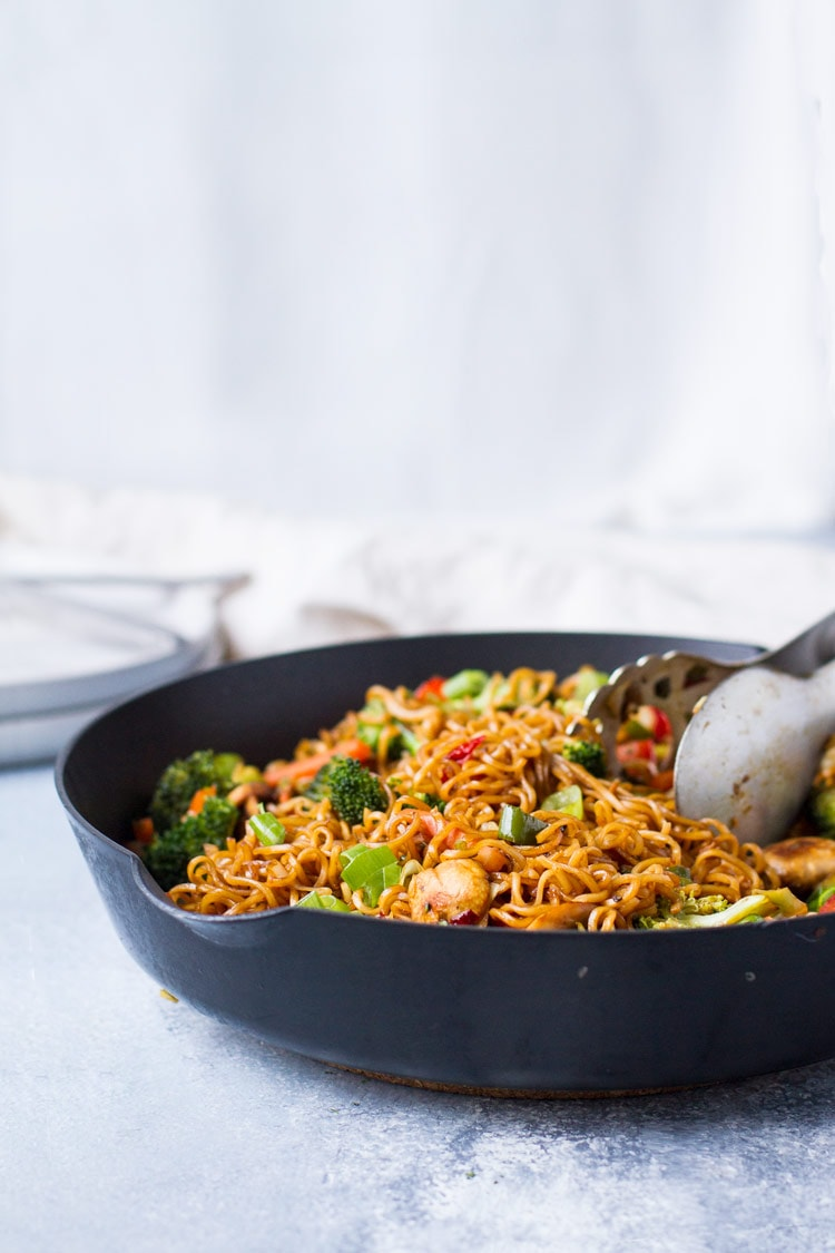Straight angle of lo mein in a skillet, white background and blue table