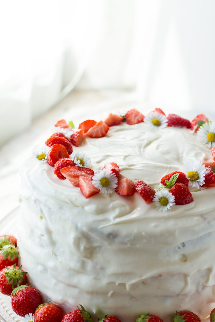 Strawberry cake with cream cheese frosting and strawberries as garnish.