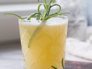Apricot Rosemary Gin Fizz in a whiskey glass.