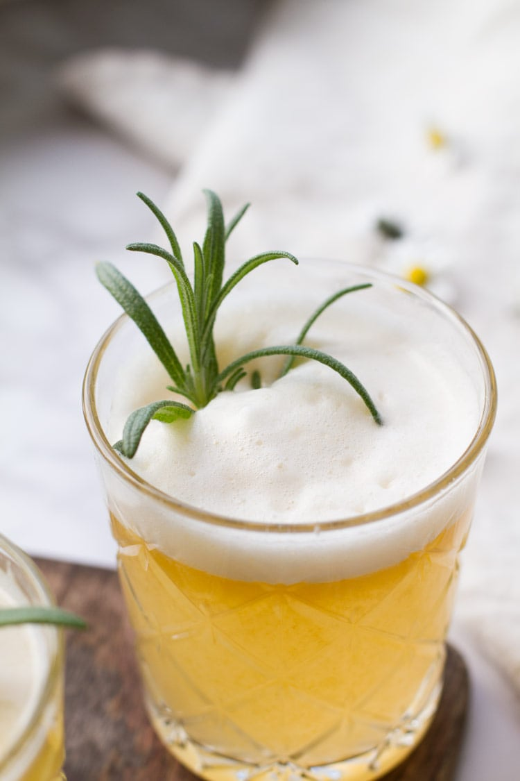 Apricot rosemary gin fizz with egg white foam and rosemary garnish.