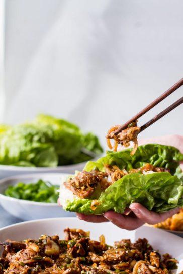 Beef bulgogi lettuce wrap adding a piece of bulgogi to it.