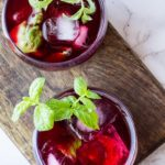 Two glasses with hibiscus tea and mint sprigs. Flatlay.