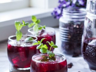 Three glasses with hibiscus tea and mint sprig garnish. Mason jar with hibiscus flowers in the background.