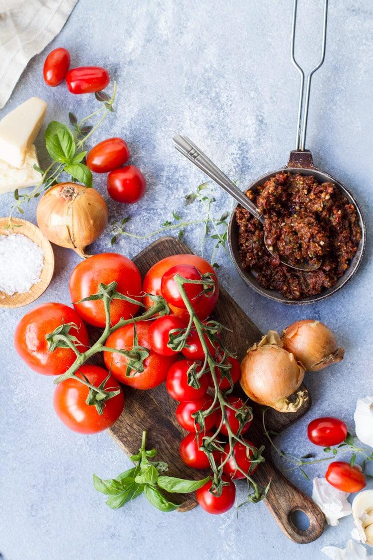 Ingredients to make roasted tomato soup; tomatoes on vines, basil, thyme, pesto etc.