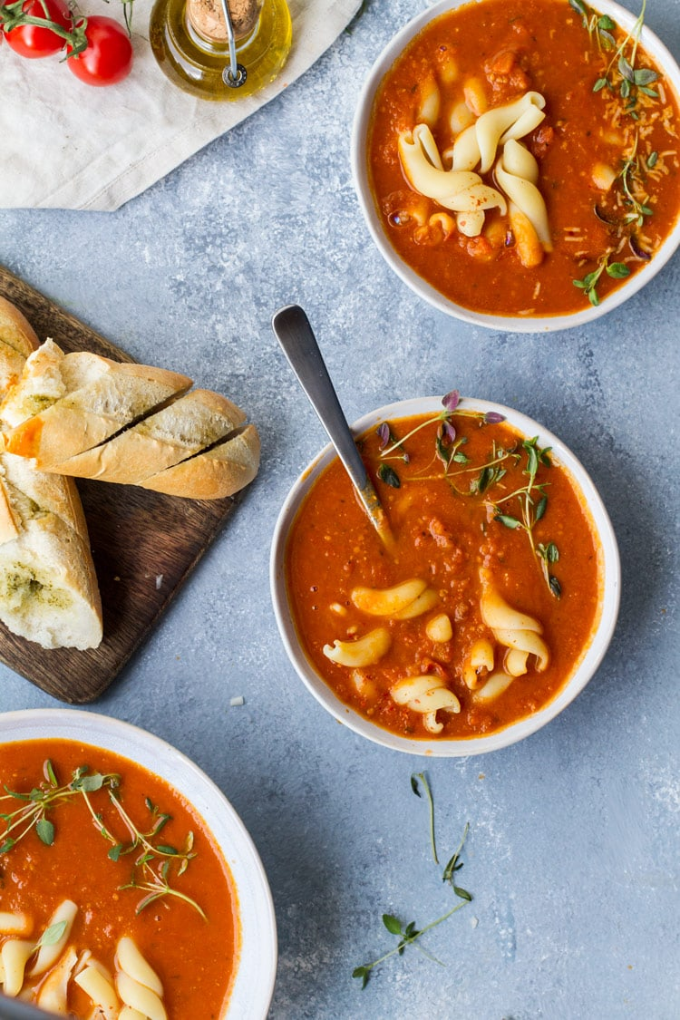 Three bowls of roasted tomato soup, garnished with pasta and fresh thyme.