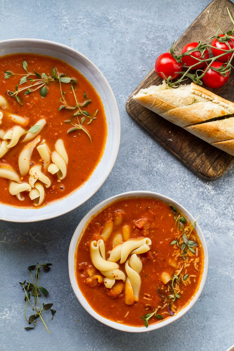 One large and one small bowl of roasted tomato soup with pasta. Garlic bread and cherry tomatoes on vine on a cutting board.