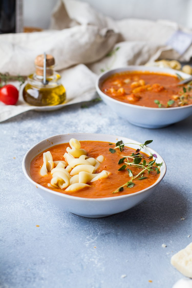 Two bowls of roasted tomato soup, pasta and fresh thyme sprig.