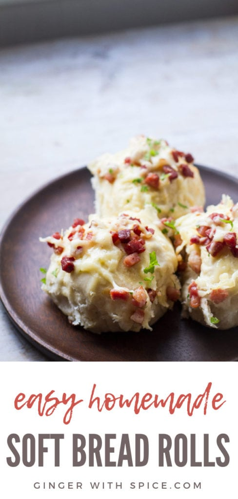 Three homemade dinner rolls with cheese and bacon on a wooden plate. Pin.