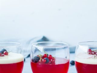 Three glasses with homemade jello, berries and two with vanilla custard. Straight on.