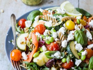 Healthy pasta salad with crumbled feta cheese, roasted tomatoes and zucchini.