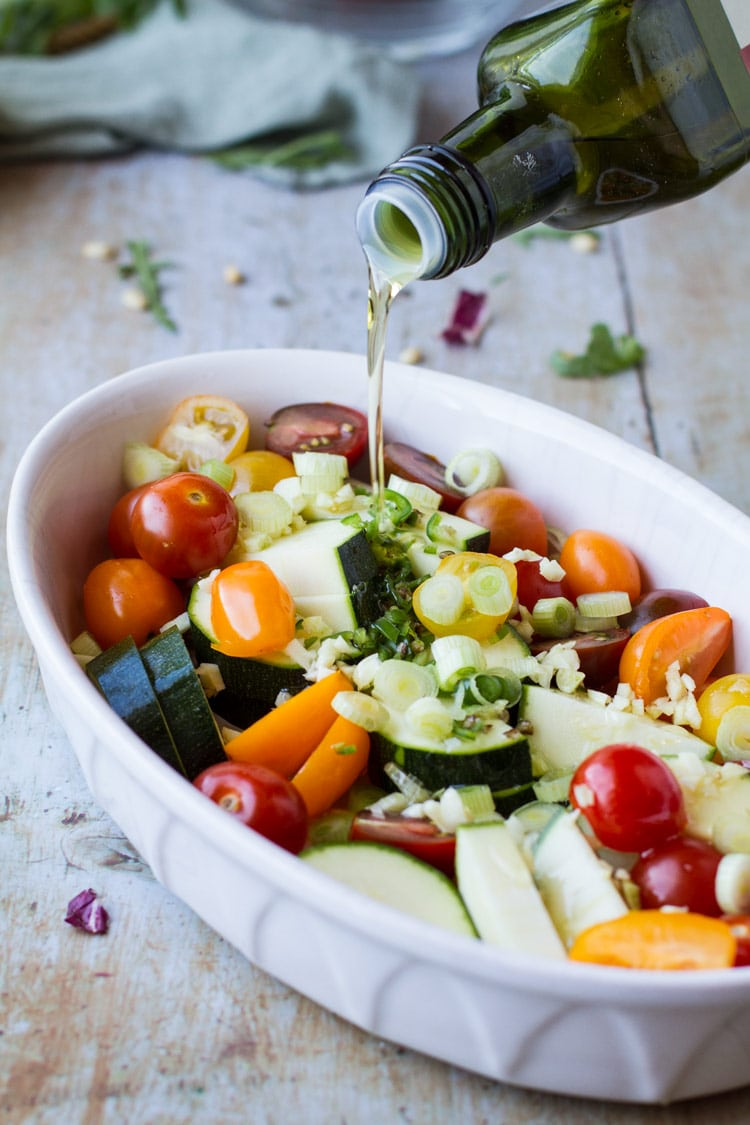 Pouring olive oil over vegetables for roasting.
