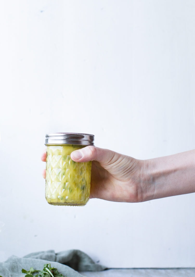 Hand holding a glass jar with a healthy pasta salad dressing.