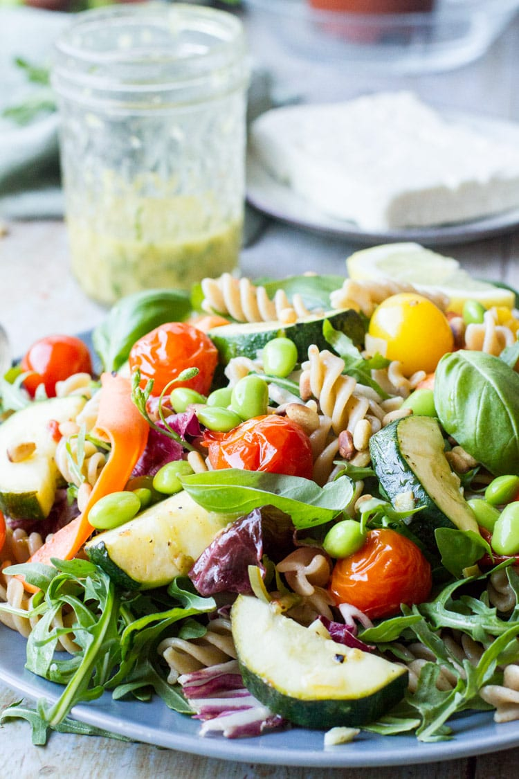 Healthy pasta salad on a dark plate, jar with pasta dressing in the background.