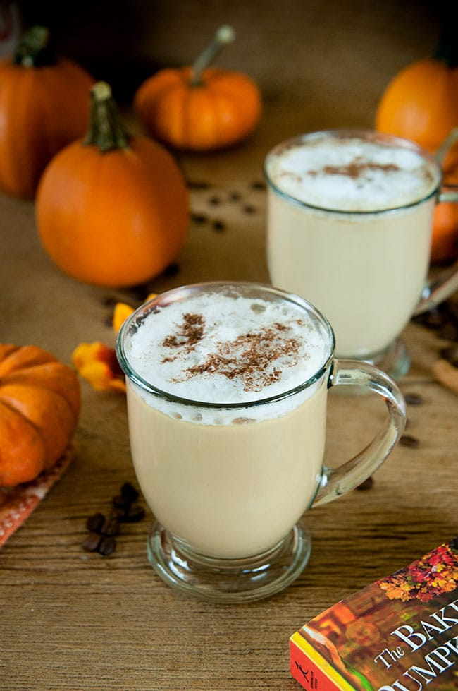 Spiked pumpkin spice latte in two clear mugs. Pumpkins as decoration in the background.