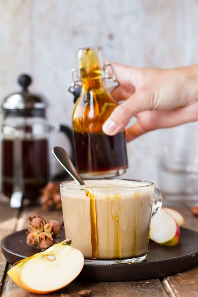 Glass cup with apple caramel latte macchiato, drizzle with caramel on the edges, hand holding glass jar with caramel in the background.