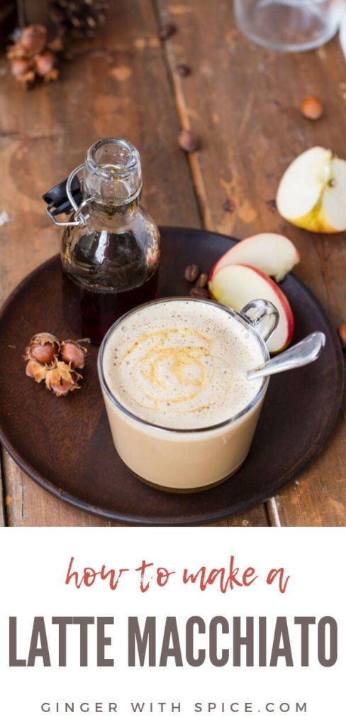 A clear mug with apple caramel latte macchiato. Glass jar with caramel sauce and apple slices on wooden plate. Pinterest pin.