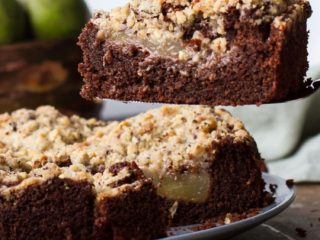 Focus on one slice of chocolate pear cake, with the whole cake in the background.