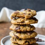 Stack of peanut butter chocolate chip cookies on a white plate, one taken a bit out of.
