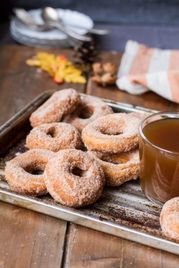 Donuts coated in cinnamon sugar and apple cider in a clear cup on a metal pan.