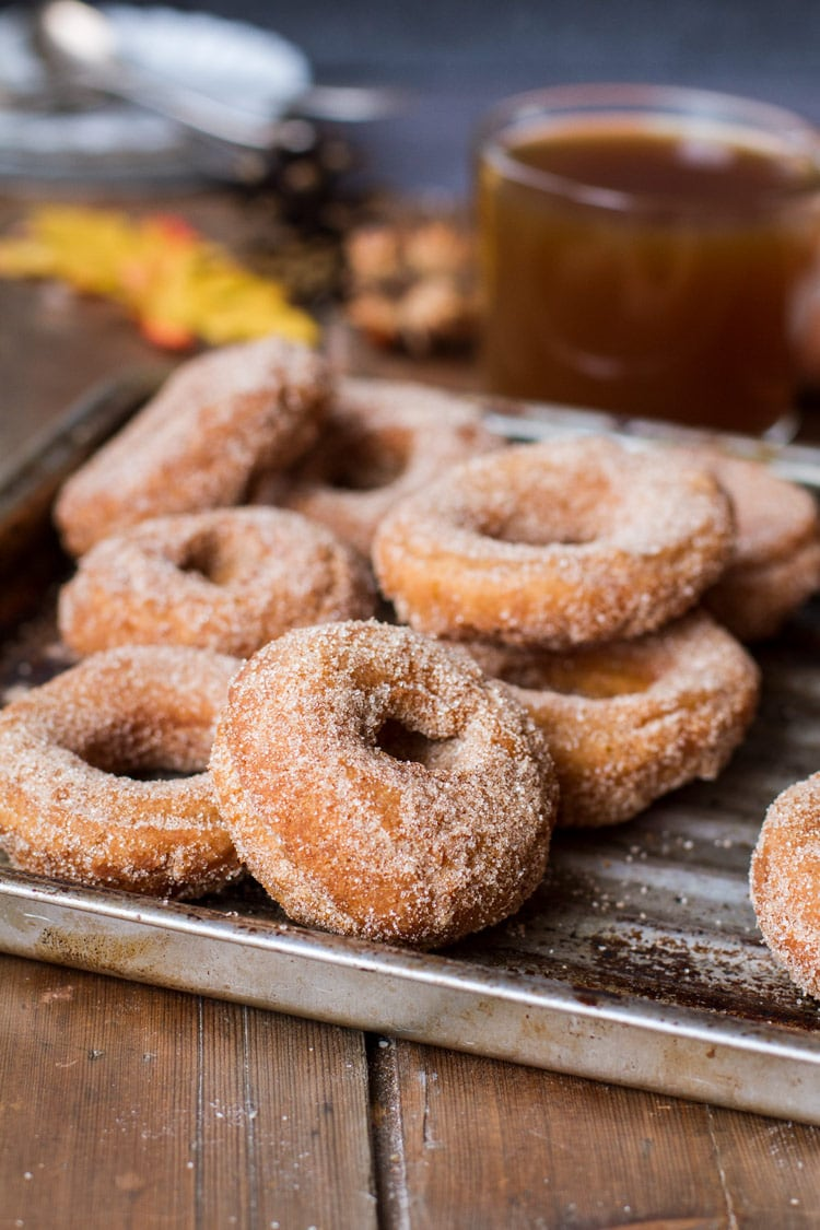 Apple Cider Donuts coated in sugar and cinnamon on a metal pan.