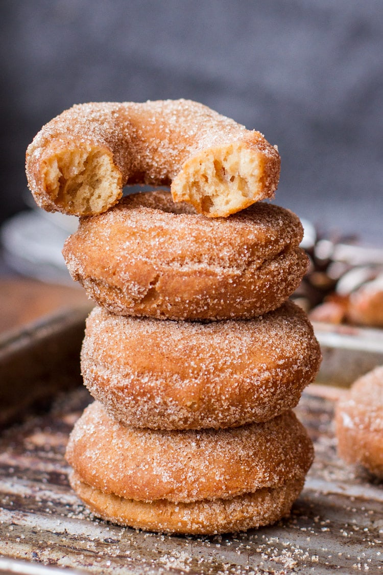 Three apple cider donuts stacked on top of each other and one half eaten on top.