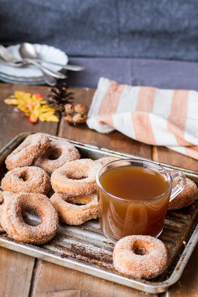 A metal pan with apple cider donuts and apple cider in a glass cup. Orange striped towel in the back.
