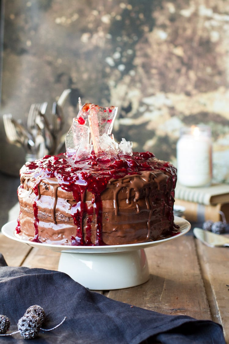 Halloween style black forest cake with sugar glass shards and cherry sauce on top.