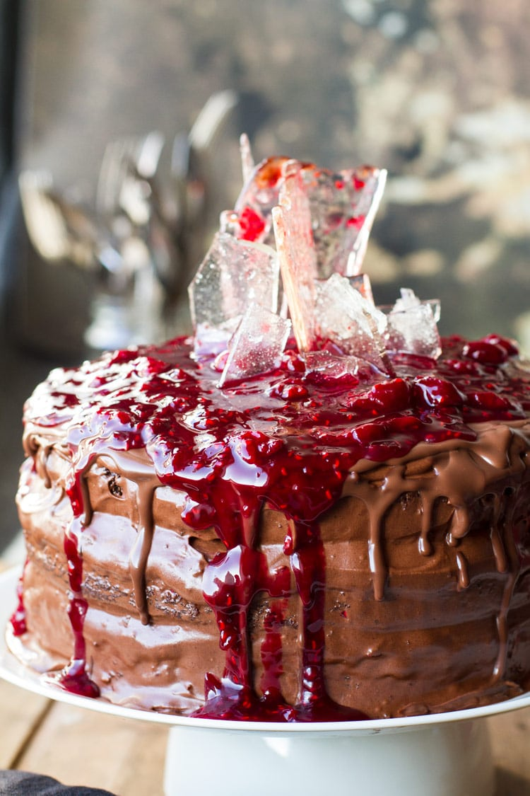 Cherry chocolate cake topped with cherry filling and sugar glass shards, close up.