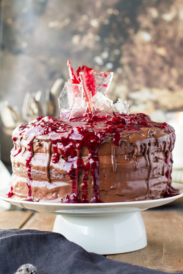 Cherry chocolate cake with sugar glass shards and cherry topping on a white cake stand.