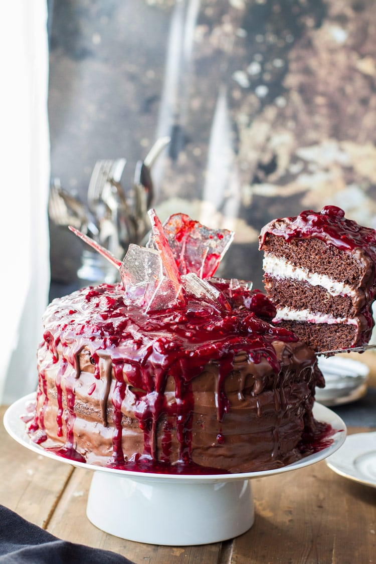 Slicing a slice of cherry chocolate cake with sugar glass shards and cherry topping (Halloween).