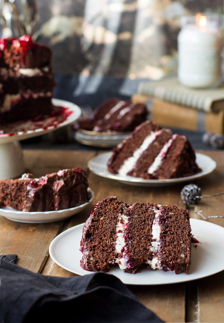 Four slices of cherry chocolate cake with layers of whipped cream and cherry filling.