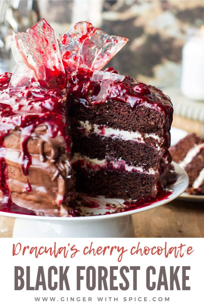 Cherry chocolate Halloween Cake cut open, showing the layers of whipped cream and cherry filling. Pinterest pin.