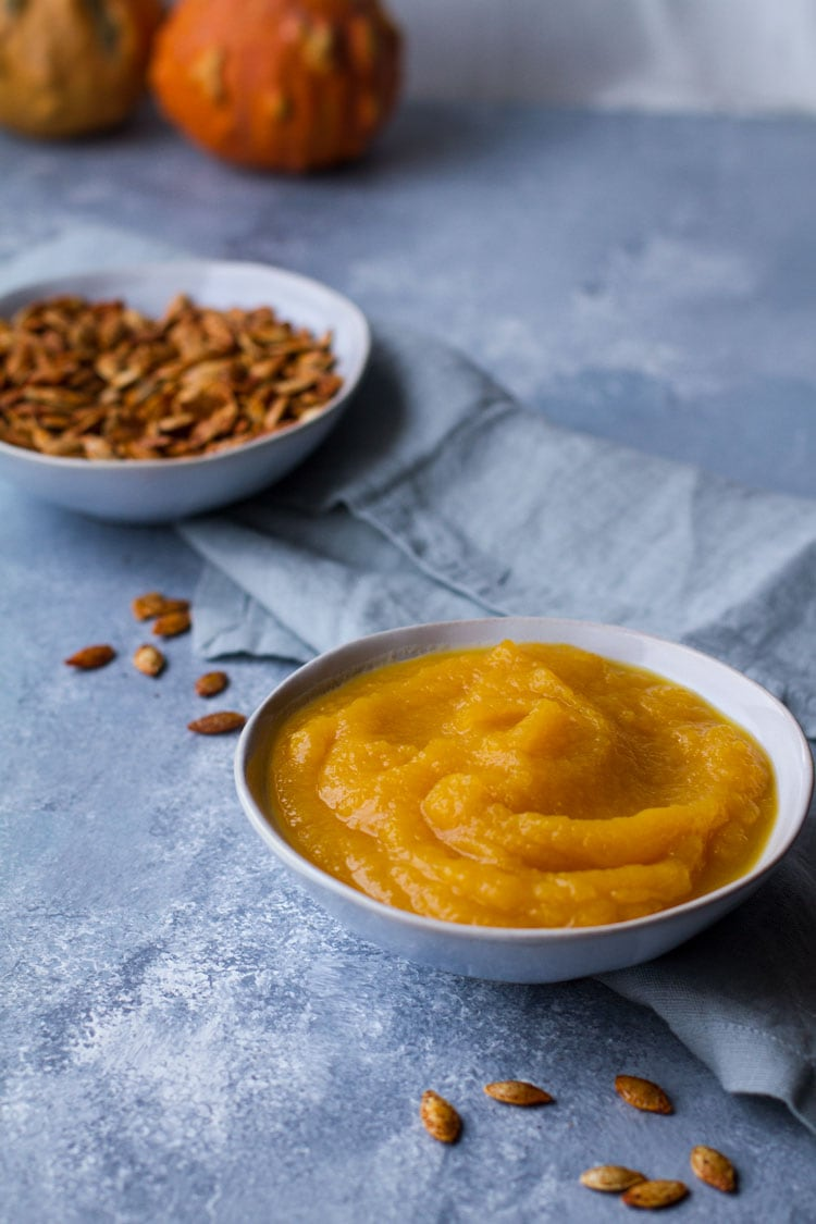Pumpkin puree in a blue bowl, blue background. Roasted pumpkin seeds in the background.