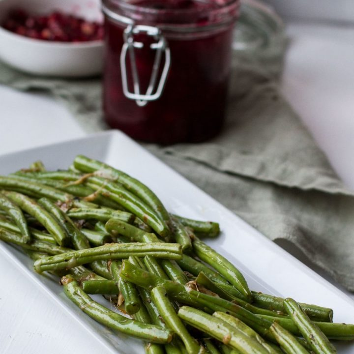 Sauteed green beans on a white, rectangular plate.