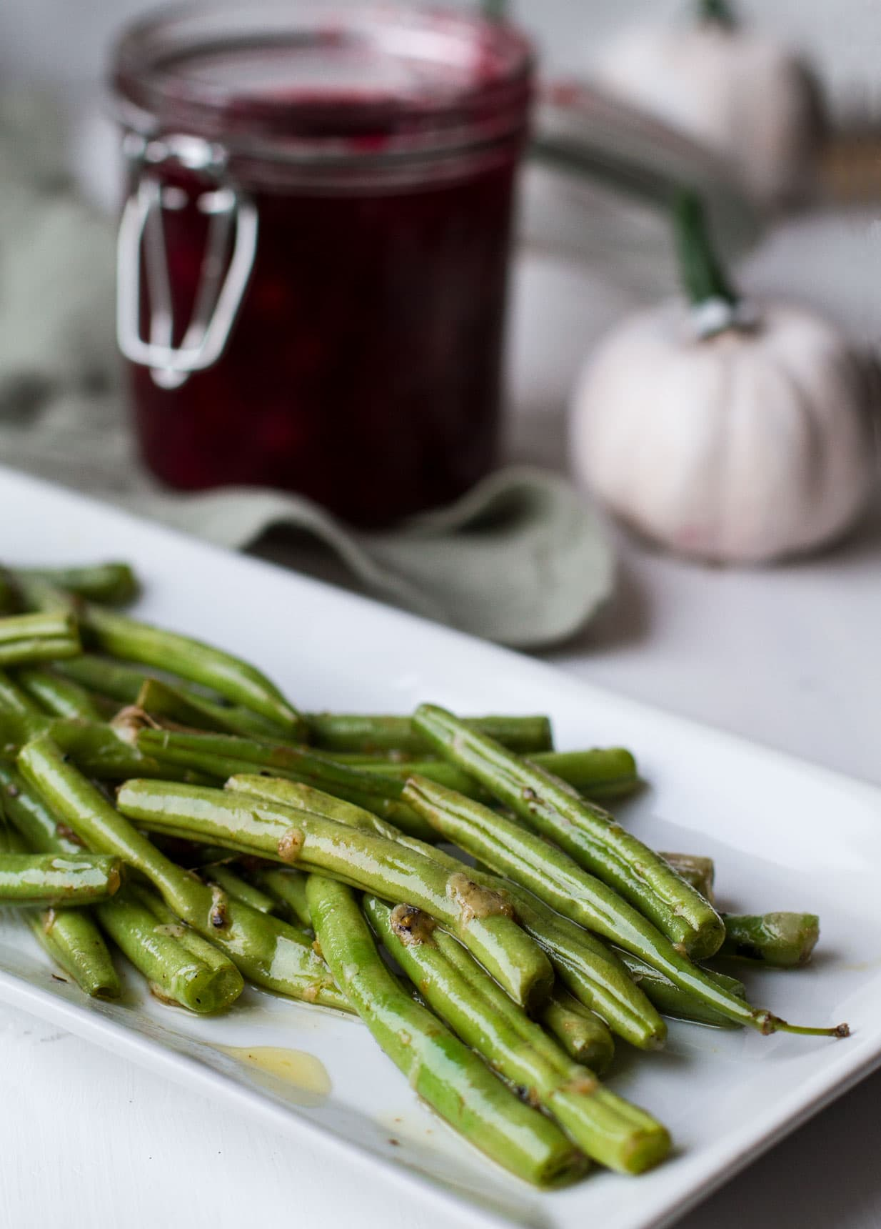 Garlic Parmesan Green Beans on a white, rectangular plate. Cranberry sauce in the background.