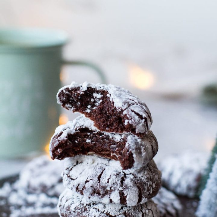 A stack of chocolate crinkle cookies, two top cookies are open in two.