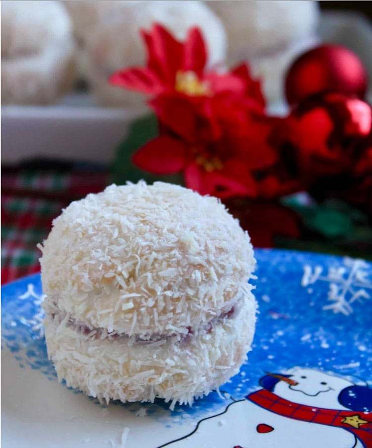 White cookies sandwiched with raspberry jam and coated in shredded coconut. On a blue snowman plate.