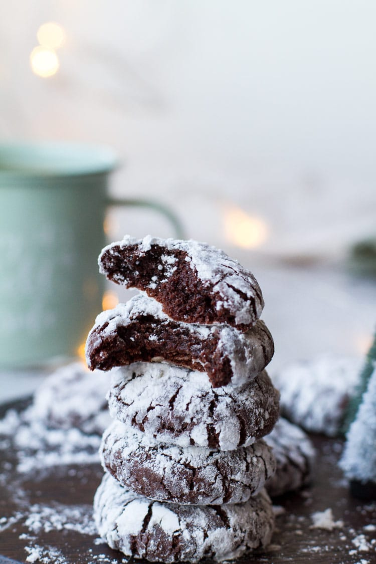 Fudgy chocolate crinkle cookies stacked, the top two are open. Turquoise mug in the background.