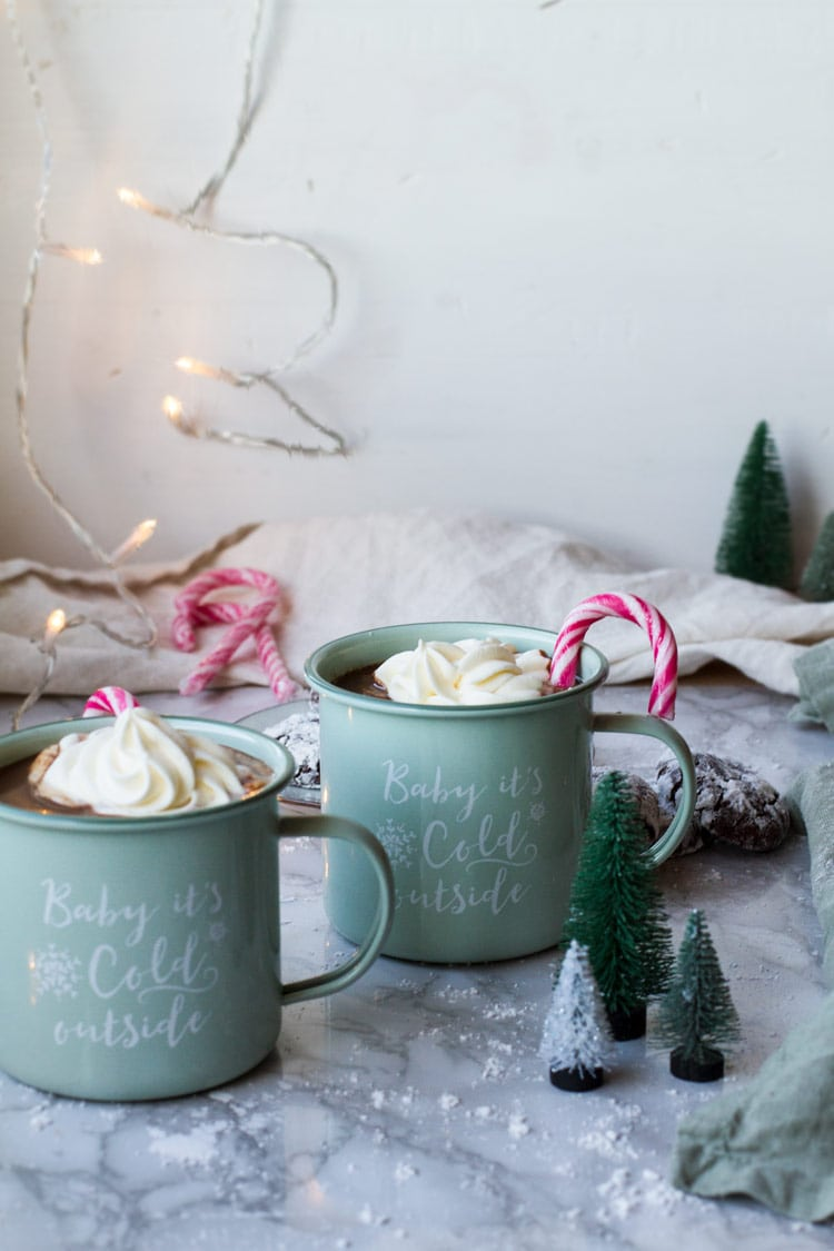 Two mint colored mugs with whipped cream and candy cane.