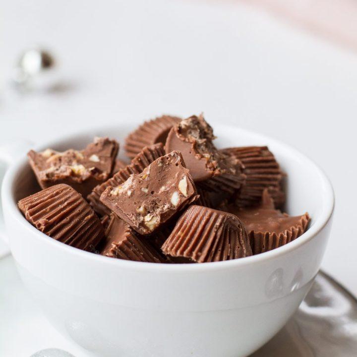 Almond Crunch Milk Chocolates, a few cut open, in a small white cup.