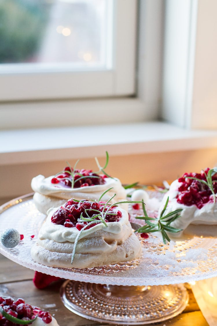Three Christmas Pavlova Desserts with eggnog cream and cherry sauce, garnished with rosemary sprigs.