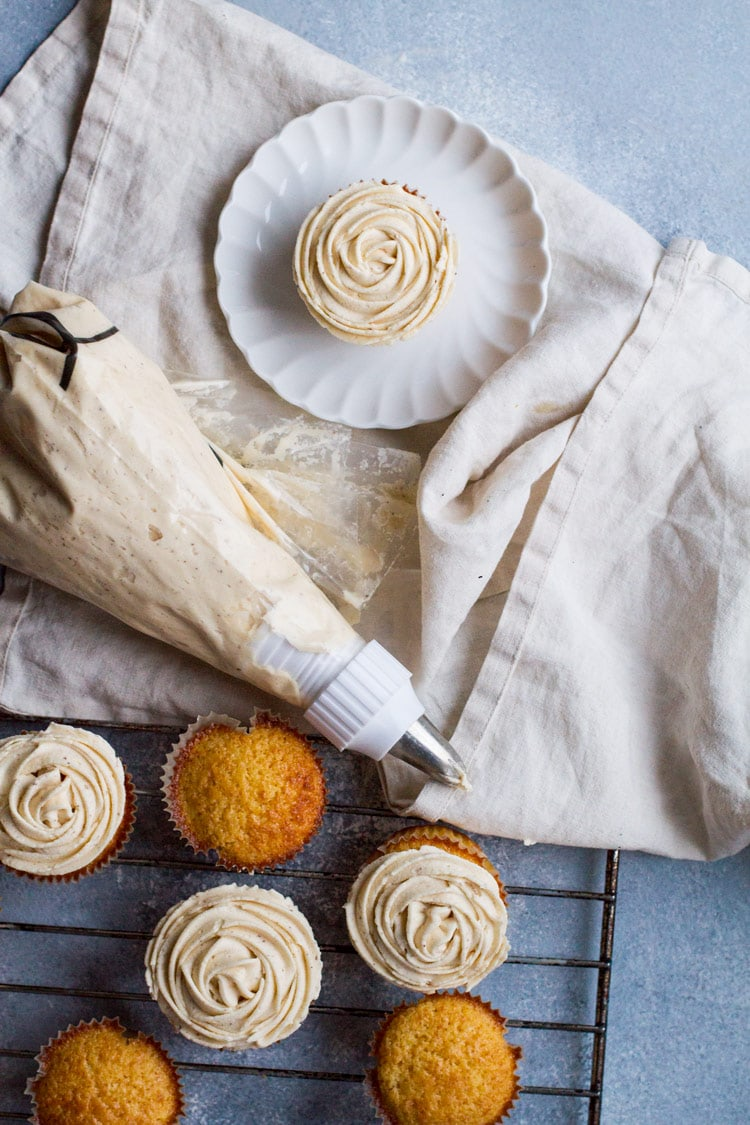 A piping bag with buttercream frosting and a cupcake frosted like a flower.