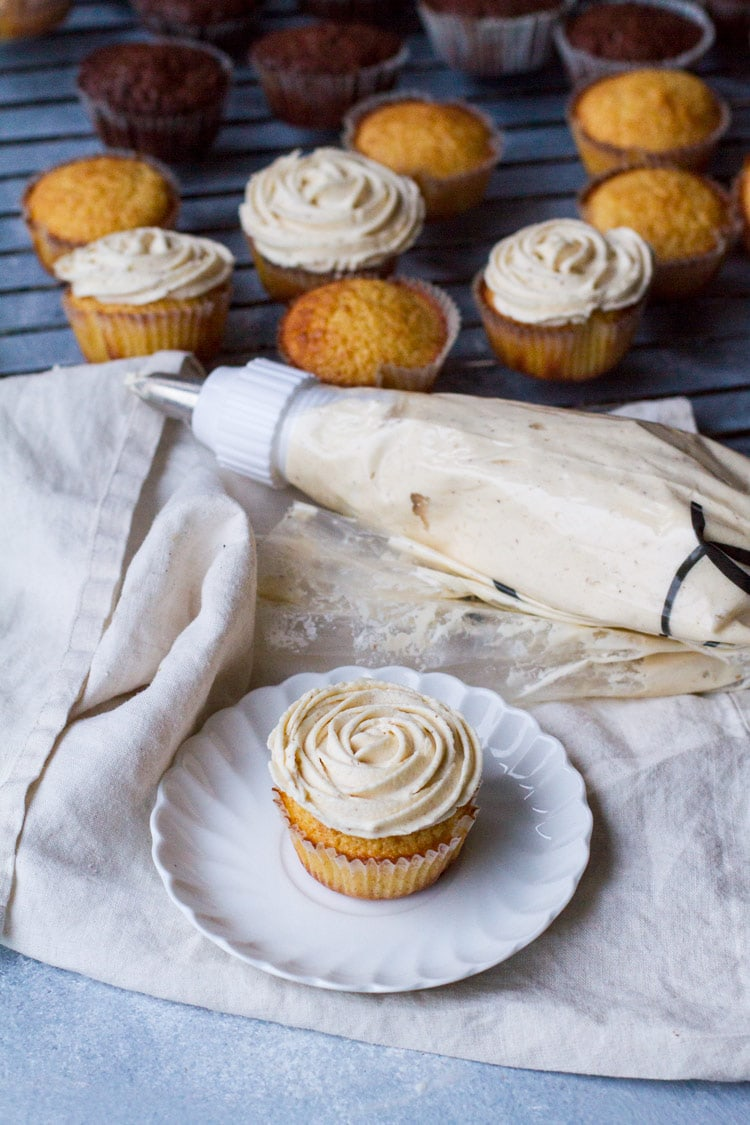 A cupcake with flower buttercream frosting on a white plate, a piping bag and muffins in the background.
