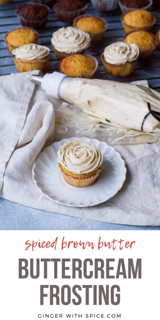 A cupcake with flower buttercream frosting on a white plate, a piping bag and muffins in the background. Pinterest pin.