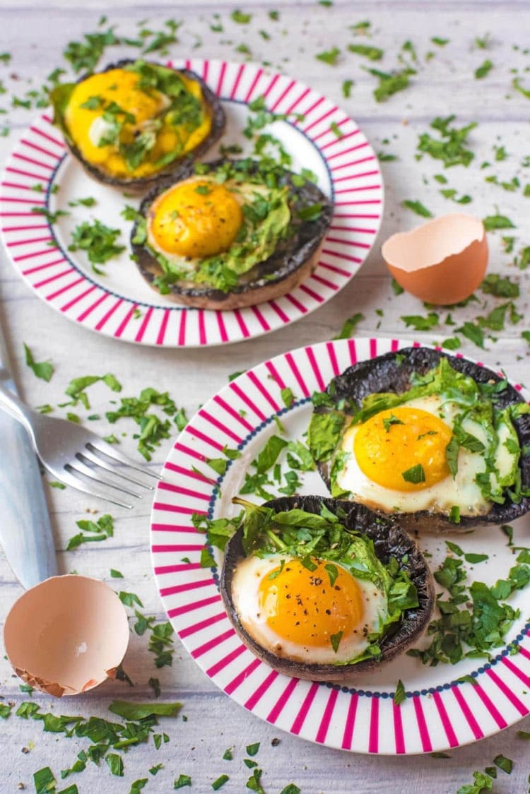 Two pink plates with two portobello mushrooms filled with baked eggs, each.